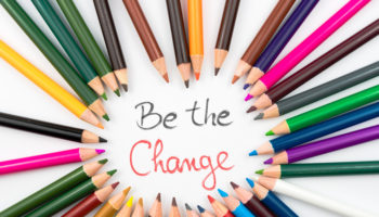 Colouring pencils in circle arrangement with message Be The Change