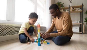 Father and son sitting on floor play with toy blocks