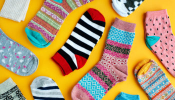Multi-colored socks on a bright background. View from above. Striped, blue, pink, patterned socks for autumn and winter. Warm clothes in the form of socks on a yellow background.