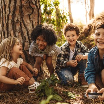 Group of cute kids playing in forest